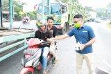 Duta BPJS Kesehatan Solok bagikan masker untuk pengendara motor dan mobil
