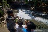 Sejumlah anak mengamati Sungai Anak Cikapundung yang tercemar limbah di Batununggal, Bandung Jawa Barat, Rabu (25/9/2019). Kondisi air aliran Sungai Anak Cikapundung yang bermuara ke Sungai Citarum tersebut berbusa dan mengeluarkan bau yang diduga akibat limbah industri sehingga menganggu aktivitas warga di sekitar sungai. ANTARA JABAR/Raisan Al Farisi/agr