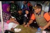 Kepala Badan Nasional Penanggulangan Bencana (BNPB) Doni Monardo (kanan) mengunjungi pasien korban gempa yang dirawat di rumah sakit lapangan yang dibangun TNI di kompleks Kampus Universitas Darussalam, Desa Tulehu, Pulau Ambon, Kabupaten Maluku Tengah, Maluku, Jumat (27/9/2019). Para pasien tersebut merupakan korban gempa bumi berkekuatan magnitudo 6,8 yang mengguncang Pulau Ambon dan sekitarnya Kamis (26/9/2019). ANTARA FOTO/Izaac Mulyawan/nym
