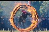 Prajurit TNI Kodam IX Udayana menerobos lingkaran api dalam atraksi halang rintang untuk memperingati HUT ke-74 TNI di Lapangan Puputan Margarana, Denpasar, Bali, Sabtu (5/10/2019). Atraksi tersebut diisi dengan spartan komando, simulasi halang rintang, bela diri militer dan keterampilan menghancurkan material guna meningkatkan kemampuan tempur para prajurit. ANTARA FOTO/Nyoman Hendra Wibowo/nym.