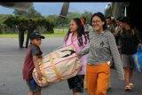 Sejumlah pengungsi mengangkat barang bawaannya ketika tiba dengan menumpang pesawat Hercules TNI AU di Bandar Udara Wamena, Papua, Rabu (9/10/2018). Sebanyak 87 orang pengungsi dari Jayapura yang didominasi warga asal Toraja tersebut kembali lagi ke Wamena. ANTARA FOTO/HO/Achmad Sugito/Humas Linjamsos/nym.