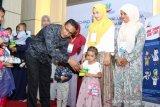 Walikota Sabang Nazaruddin menyerahkan buku tabungan Bank Aceh Syariah kepada sejumlah anak saat peluncuran program bantuan tunai dana Geunaseh di Sabang, Aceh, kamis (10/10/2019). Pemerintah kota Sabang meluncurkan dana Gerakan Untuk Anak Sehat (Geunaseh) Sabang dalam upaya mengatasi malnutrisi dan stunting di wilayah tersebut. Antara Aceh/Khalis Surry