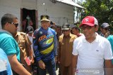 Plt Gubernur Aceh Nova Iriansyah (tiga kiri) bersama Bupati Aceh Barat Ramli MS (tiga kanan) melintas di depan rumah warga seusai meresmikan dan menyalakan operasional  jaringan listrik perdana di Desa Sikundo, Kecamatan Pantee Ceureumen, Aceh Barat, Aceh. Foto/Syifa Yulinnas.
