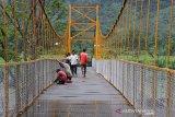 Pekerja menyelesaikan pembangunan jembatan gantung di Desa Sikundo, Kecamatan Pante Ceureumen, Aceh Barat, Aceh. Foto/Syifa Yulinnas.