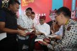 Bupati Banyuwangi Abdullah Azwar Anas (tengah) menandatangani buku