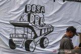 Warga melintas di depan spanduk Dosa DPR saat unjuk rasa damai di depan Gedung Sate, Bandung, Jawa Barat, Kamis (17/10/2019). Aksi tersebut untuk menyampaikan aspirasi terhadap sejumlah permasalahan di Indonesia dan menuntut dicabutnya sejumlah RUU bermasalah seperti RKUHP. RUU  Minerba, serta segera diterbitkannya Perppu KPK. ANTARA JABAR/Novrian Arbi/agr