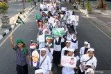 Santri membawa sejumlah poster tokoh Nahdlatul Ulama pada pawai peringatan Hari Santri Nasional di Sidoarjo, Jawa Timur, Minggu (20/10/2019). Kegiatan yang diikuti oleh ribuan santri dan guru dari berbagai sekolah dan pesantren tersebut untuk memperingati Hari Santri Nasional. Antara Jatim/Umarul Faruq/zk