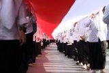 Santri membawa bendera merah putih sepanjang 1000 meter saat pawai peringatan Hari Santri Nasional di Sidoarjo, Jawa Timur, Minggu (20/10/2019). Kegiatan yang diikuti oleh ribuan santri dan guru dari berbagai sekolah dan pesantren tersebut untuk memperingati Hari Santri Nasional. Antara Jatim/Umarul Faruq/zk
