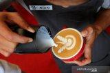 Barista membuat gambar dengan susu diatas kopi arabika pada perlombaan seni latte di Blangpadang, Banda Aceh, Aceh, Minggu (20/10/2019). Perlombaan seni latte yang dilaksanakan pada festival kopi Banda Aceh 2019 bertujuan meningkatkan kemampuan barista lokal dalam menyajikan kopi arabika gayo. Antara Aceh/Irwansyah Putra.