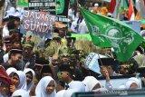 Sejumlah santri mengikuti Kirab Hari Santri Nasional 2019 di Lapang Dadaha, Kota Tasikmalaya, Jawa Barat, Selasa (22/10/2019). Kirab santri yang diikuti ribuan santri dari berbagai pondok pesantren se-Tasikmalaya dalam rangka memperingati hari santri nasional dengan menjadi momentum membangun optimisme santri Indonesia menjadi garda terdepan dalam menjaga nilai-nilai keberagamaan dan kebangsaan. ANTARA FOTO/Adeng Bustomi/agr