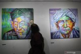Pengunjung melihat lukisan berjudul KH Hasyim Asy'ari (kiri) dan KH Wahab Hasbullah (kanan) karya Luqman Hidayat saat pameran seni rupa Jawa Timur 2019 bertajuk