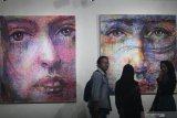 Pengunjung melihat lukisan berjudul Tatapan karya Agung Irawan saat pameran seni rupa Jawa Timur 2019 bertajuk