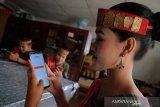 Seorang wanita mengenakan pakaian adat Batak Toba menggunakan layanan internet banking didampingi dua rekannya di sela kegiatan Lembaga Penjamin Simpanan (LPS) Peduli