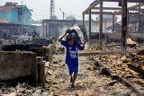 Seorang anak kecil membawa  barang-barang yang bisa digunakan pasca kebakaran di Pasar Jatisari, Karawang, Jawa Barat, Jumat (25/10/2019). Pemerintah Kabupaten Karawang berencana merelokasi para pedagang sebagai solusi jangka pendek dan akan membagunan ulang pasar tersebut guna mengembalikan perekonomian masyarakat. ANTARA JABAR/M Ibnu Chazar/agr