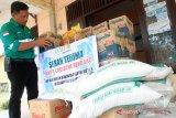 Manager External Relations PT Mifa Bersaudara Azizon Nurza (kiri) menata bantuan untuk korban banjir di Desa Cot Amun, Kecamatan Samatiga, Aceh Barat, Aceh, Selasa (5/11/2019). Perusahaan pertambangan batu bara PT Mifa Bersaudara menyalurkan bantuan berupa bahan pangan logistik untuk korban banjir yang tersebar di Kecamatan Woyla Timur, Arongan Lam Balek dan Kecamatan Samatiga sebagai bentuk kepedulian dan meringankan beban masyarakat korban banjir. ANTARA FOTO/Syifa Yulinnas.