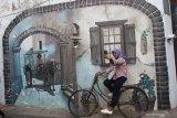 Pengunjung melakukan swafoto di salah satu sudut Kampung Wisata Heritage, Kayutangan, Malang, Jawa Timur, Kamis (7/11/2019).  Warga di pemukiman tersebut merubah lingkungannya menjadi kampung wisata dengan mengandalkan keunikan bangunan bersejarah dipadu dengan kumpulan barang antik untuk menarik wisatawan agar datang berkunjung. Antara Jatim/Ari Bowo Sucipto/zk.