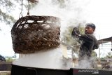 Perajin memindahkan keranjang berisi ikan tongkol seusai direbus saat proses pengeringan menggunakan panas matahari di salah satu usaha industri rumahan, Desa Gano, Kecamatan Syiah Kuala, Banda Aceh, Aceh, Jumat (8/11/2019). Menurut perajin, dampak dari perubahan cuaca yang memasuki musim penghujan, pmengakibat roduksi ikan kayu saat ini menurun dari empat ton menjadi tiga ton perbulan dengan harga penjualan Rp30.000 perkilogram. Antara Aceh/Ampelsa.