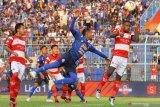 Pesepak bola Arema FC,  Sunarto (tengah)  berebut bola dengan pesepak bola Madura United, Alfath Faathier (kanan) dalam pertandingan Liga I di Stadion Kanjuruhan, Malang, Jawa Timur, Jumat (8/11/2019).Arema menaklukkan Madura United dengan skor akhir 2-0. Antara Jatim/Ari Bowo Sucipto/zk.