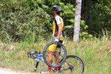 Seorang pebalap memegang roda sepedanya yang rusak saat mengikuti iven Tour De Singkarak 2019 etape delapan, Kota Sungai Penuh, Jambi, Sabtu (9/11/2019). Etape kedelapan dengan rute Sungai Penuh-Pesisir Selatan dengan panjang lintasan 212.9 kilometer, dimenangkan NovardiantoJamalidin dari PGN Road Cycling Team dengan catatan waktu 5.04.46. disusul Rustom Lim dari tim 7eleven Cliqq Air21 by Roadbike Philippines dengan catatan waktu 5.04.06 dan Jesse Ewart dari Sapura Cycling Team pada posisi tiga dengan catatan waktu 5.5.56. ANTARA FOTO/Muhammad Arif Pribadi/foc.