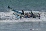 Sejumlah nelayan bergotong royong mendorong perahu berkapasitas 7 Gross Tonnage (GT) di Pesisir Pantai Timur Pangandaran, Jawa Barat, Senin (11/11/2019). Kementerian Kelautan dan Perikanan mendorong pemilik kapal untuk mengasuransikan anak buah kapal (ABK) dengan menargetkan 160.000 fasilitasi asuransi untuk nelayan kecil atau kapal di bawah 10 GT, sedangkan sampai saat tercatat hanya 88.000 nelayan yang disetujui asuransinya. ANTARA JABAR/Adeng Bustomi/agr