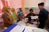 Pasien rawat inap RSUZA (dua kanan) asal kabupaten Bireuen menerima kartu BPJS kesehatah, KTP dan kartu keluarga yang diserahkan Ketua DPRK Banda Aceh Farid Nyak Umar (kanan) didampingi anggota DPR Aceh dari PKS Purnama Setia Budi (tiga kiri) dan Kepala Dinas Kependudukan dan Catatan Sipil Kota Banda Aceh Emilia Sovayana (kiri) di Banda Aceh, Aceh, Senin (11/11/2019). Pemerintah Kabupaten Bireuen dan Pemerintah Kota Banda Aceh bekerjasama membuat kartu identitas warga yang sedang rawat inap guna mendapat kartu BPJS kesehatan yang disubsidi Pemerintah. Antara Aceh/Irwansyah Putra.