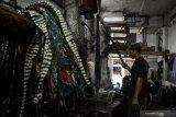 Pekerja melarutkan malam pada kain batik tulis di sebuah industri rumahan di Kampoeng Batik Jetis, Sidoarjo, Jawa Timur, Selasa (12/11/2019). Produksi batik pada musim kemarau seperti saat ini meningkat hingga 50 persen dibanding saat musim hujan, karena proses pengeringan lebih cepat. Antara Jatim/Umarul Faruq/zk