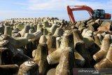 Sejumlah pekerja melakukan pemasangan batu pemecah ombak saat pembangunan tanggul pengaman pantai di Desa Suak Timah, Kecamatan Samatiga, Aceh Barat, Selasa (12/11/2019). Pembangunan tanggul pengaman pantai tersebut untuk mengatasi penurunan permukaan tanah di sepanjang pantai sekaligus untuk memajukan perekonomian masyarakat pesisir baik dari sektor pendapatan nelayan, wisata serta pengelolaan sumber daya alam ekosistem pantai. Antara Aceh/Syifa Yulinnas.