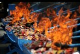 Petugas memusnahkan barang bukti rokok ilegal di Kantor Pengawasan dan Pelayanan Bea dan Cukai Tipe Madya Pabean A Denpasar, Bali, Rabu (13/11/2019). Bea dan Cukai Denpasar memusnahkan berbagai Barang Milik Negara hasil penindakan periode Januari-Agustus 2019 seperti 626 botol Minuman Mengandung Etil Alkohol (MMEA), 328.908 batang rokok, 157 botol cairan rokok elektronik, 741 unit alat kesehatan dan 1.369 produk kosmetik dengan total kerugian negara sekitar Rp1,3 miliar. ANTARA FOTO/Fikri Yusuf/nym.