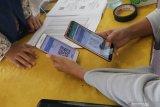 Petugas melakukan scan Guick Response (QR) kode dari gawai milik pencari kerja saat bursa kerja di halaman Dinas Tenaga Kerja, Kediri, Jawa Timur, Rabu (13/11/2019). Pemerintah daerah setempat rutin menyelenggarakan bursa kerja sekaligus memberikan layanan online digitalisasi curriculum vitae (CV), ijazah, dan berkas pendukung lainnya yang dapat diakses oleh pencari kerja ataupun perusahaan pembuka lowongan kerja melalui scan QR kode sehingga lebih praktis karena tidak memerlukan berkas fisik. Antara Jatim/Prasetia Fauzani/zk.