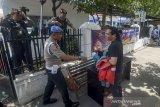 Petugas Kepolisian meminta pengunjung untuk menunjukan isi tas nya sebelum memasuki Polrestabes Bandung, Jawa Barat, Rabu (13/11/2019). Polrestabes Bandung memperketat pengamanan pascaledakan bom bunuh diri di mapolrestabes Medan pada Rabu pagi. ANTARA FOTO/Raisan Al Farisi/agr