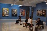 Pengunjung mengamati lukisan saat pameran tunggal pelukis Asri Noegroho di Indigo Art Space Madiun, Jawa Timur, Minggu (17/11/2019) malam. Pameran lukisan karya pelukis asal Surabaya bertema Tokoh tersebut akan berlangsung hingga 8 Desember 2019. Antara Jatim/Siswowidodo/zk