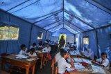Sejumlah siswa SDN 2 Kadupandak belajar didalam tenda darurat di Desa Kadupandak, Kecamatan Tambaksari, Kabupaten Ciamis, Jawa Barat, Senin (18/11/2019). Sebanyak 35 siswa terpaksa mengikuti kegiatan belajar mengajar menggunakan tenda darurat meskipun dalam kondisi panas dan berdebu akibat sekolahya terancam roboh karena pergerakan tanah. ANTARA JABAR/Adeng Bustomi/agr