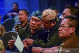 Gubernur Jawa Barat Ridwan Kamil (kiri) berbincang dengan Ketua Bawaslu Jabar Abdullah Dahlan (tengah) saat acara peluncuran pengawasan pilkada serentak di Bandung, Jawa Barat, Rabu (20/11/2019). Peluncuran tersebut merupakan bagian dari Bawaslu untuk menginformasikan kepada seluruh masyarakat bahwa pelaksanaan pengawasan pemilu di tujuh Kabupaten dan satu Kota di Jawa Barat telah dimulai dan akan dilaksanakan pada 23 September 2020 mendatang. ANTARA FOTO/Raisan Al Farisi/agr