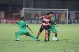 Pesepak bola Madura United (MU) Diego Assis (tengah) berusaha melewati pesepak bola Bhayangkara Fc Nur Iskandar (kiri) dan TM  Ichsan (kanan) dalam laga Shopee Liga 1 di Stadion Gelora Bangkalan (SGB) Bangkalan, Jawa Timur, Jumat (22/11/2019). Bhayangkara FC memenangi pertandingan tersebut dengan skor 2-1. Antara Jatim/Saiful Bahri/zk.