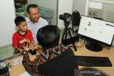 Atase Imigrasi Konsulat Jenderal Republik Indonesia (KJRI) Kuching Sarawak Ronny Fajar Purba (kanan) mendampingi Akbar (kedua kanan), satu dari enam Warga Negara Indonesia yang dievakuasi dari hutan saat perekaman data di Kantor KJRI Kuching, Sarawak, Malaysia, Kamis (21/11/2019). Ronny Fajar Purba menyatakan pihaknya membuatkan dokumen perjalanan berupa Surat Perjalanan Laksana Paspor (SPLP) untuk Mildah Situmorang beserta kelima anaknya (Diana, Akbar, Murni, Linda, Puteri), WNI asal Tebing Tinggi, Sumatra Utara yang ditemukan dalam kondisi terlantar di sebuah pondok di hutan Batu Sembilan Bintulu dan selanjutnya akan dipulangkan ke Indonesia.  ANTARA FOTO/HS Putra/jhw