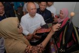 Menteri Koperasi dan Usaha Kecil Menengah (UKM) Teten Masduki (kedua kiri) melihat produk tas karya perajin UMKM disela Forum Bisnis Muhammadiyah Internasional 2019 di Denpasar, Bali, Senin (25/11/2019). Kegiatan yang digelar pada 25-27 November 2019 tersebut diikuti para pelaku UMKM untuk memperkenalkan produk serta menggerakan ekonomi mandiri. ANTARA FOTO/Nyoman Hendra Wibowo/nym.