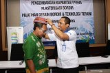 Wakil Pimpinan Permodalan Nasional Madani (PNM) Cabang Surabaya Sugiarto (kanan) memasangkan kopyah bordir kapada Kasi Industri tekstil dan kimia aneka disperindag Pasuruan Misbakhul Munir (kiri) saat pelatihan desain bordir dan teknologi terkini program pengembangan kapasitas usaha Klasterisasi bordir di Bangil, Pasuruan, Jawa Timur, Kamis (28/11/2019). Program yang diadakan oleh PT PNM di daerah tersebut bertujuan untuk meningkatkan daya saing pasar pada usaha bordir melalui pelatihan desain dengan menggunakan teknologi terkini. Antara Jatim/Umarul Faruq/zk