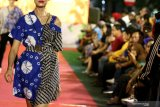 Peragawati memamerkan busana yang dikenakannya pada Peragaan Busana Di Jalan (Fashion on The Street) saat 'Mlaku-Mlaku Nang Tunjungan' di Jalan Tunjungan, Surabaya, Jawa Timur, Minggu (1/12/2019). Peragaan busana itu memamerkan sejumlah busana karya 28 pelaku usaha busana Pahlawan Ekonomi dan Pejuang Muda Pemkot Surabaya. Antara Jatim/Didik/ZK