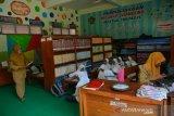 Siswa kelas 3 mengikuti proses belajar secara lesehan di ruang perpustakaan MTs Negeri 12 Desa Nglele, Kecamatan Sumobito, Jombang, Jawa Timur, Senin (2/12/2019). Sambil menunggu perbaikan ruang kelas yang rusak akibat diterjang angin kencang, proses kegiatan belajar mengajar siswa kelas 3 MTs Negeri 12 Jombang terpaksa dipindahkan sementara ke ruang perpustakaan. Antara Jatim/Syaiful Arif/zk.