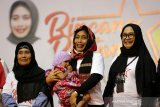 Menteri Pemberdayaan Perempuan dan Perlindungan Anak (PPPA) I Gusti Ayu Bintang Puspayoga (tengah) menggendong anak pelaku usaha rumah tangga saat berdialog tentang program Membina Ekonomi Keluarga Sejahtera (Mekaar) PT Permodalan Nasional Madani (PNM) di Amel Convention Hall, Banda Aceh, Aceh, Kamis (5/12/2019). Pada kunjungan perdana sejak menjabat Menteri PPPA ke provinsi Aceh Bintang Puspayoga mengajak seluruh perempuan untuk mandiri secara ekonomi guna meningkatkan kesejahteraan dan mencegah kekerasan dalam keluarga. Antara Aceh/Irwansyah Putra.