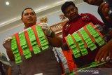 Kapolres Jombang, AKBP Boby P Tambunan (kiri), Kasubag Humas AKP Hariono (kanan) menunjukkan barang bukti obat penenang riklona clonazepam saat rilis ungkap kasus narkotika di Mapolres Jombang, Jawa Timur, Jumat (6/12/2019). Satreskoba Polres Jombang berhasil mengungkap kasus peredaran narkotika dengan barang bukti sebanyak 42,23 gram sabu, 23 ribu butir pil dobel L dan 490 butir obat penenang riklona clonazepam dari tiga orang pelaku. Antara Jatim/Syaiful Arif/zk.