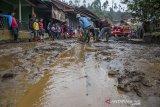 Warga membersihkan lumpur yang menutupi jalan pascabanjir bandang di Kertasari, Kabupaten Bandung, Jawa Barat, Sabtu (7/12/2019). Sedikitnya 20 rumah dan lahan pertanian di kawasan tersebut mengalami kerusakan serta terendam lumpur akibat banjir bandang yang terjadi pada Jumat (6/12) lalu. ANTARA JABAR/Novrian Arbi/agr