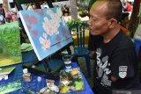 Pelukis penyandang disabilitas Agus Yusuf melukis menggunakan mulut saat digelar Gebyar Difabel 2019 di Kota Madiun, Jawa Timur, Minggu (8/12/2019). Gebyar Difabel yang digelar Komunitas Orangtua Anak Spesial Madiun dalam rangka memperingati Hari Disabilitas Internasional tersebut diikuti ratusan penyandang disabilitas terdiri pelajar dan masyarakat umum. Antara Jatim/Siswowidodo/zk