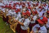 Sejumlah siswa Sekolah Dasar Negeri (SDN) se-Kota Tasikmalaya memainkan angklung dalam rangka memeriahkan hari angklung sedunia (Angklung Day) yang ke-9 di Balekota Tasikmalaya, Jawa Barat, Senin (9/12/2019). Memainkan angklung massal yang diikuti 2019 siswa bertujuan agar generasi penerus tidak melupakan kesenian musik tradisional dan diharapkan bisa mempertahankan serta mengembangkan kesenian angklung dari upaya pelestarian kearifan lokal. ANTARA JABAR/Adeng Bustomi/agr