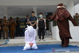 Terpidana pelanggar hukum Syariat Islam (kiri) menjalani eksekusi cambuk di Taman Sari, Banda Aceh, Selasa (10/12/2019). Terpidana dalam kasus khalwat di salah satu hotel bintang lima di Banda Aceh itu dikenakan hukuman enam kali cambuk setelah dipotong masa tahanan, sedangkan pasangan terpidana dari oknum TNI kasusnya masih ditangani oleh Polisi Militer dan Polri. Antara Aceh/Ampelsa.