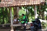 Pekerja ojek daring mengantar obat ke salah satu tempat pasien di Banyuwangi, Jawa Timur, Rabu (11/12/2019). Pemerintah daerah Banyuwangi bekerja sama dengan perusahaan ojek daring Gojek menciptakan inovasi Gancang Aron untuk mengantar obat secara gratis ke rumah pasien kurang mampu. Antara Jatim/Budi Candra Setya/zk.