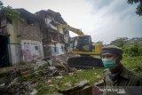 Petugas mengoperasikan alat berat untuk menghancurkan rumah saat penggusuran permukiman Tamansari, Bandung, Jawa Barat, Kamis (12/12/2019). Upaya penggusuran tersebut berakhir ricuh setelah Satpol PP memaksa warga dan aktivis mahasiswa untuk mengosongkan tempat tinggalnya di lahan sengketa yang dimana proses sidang sengketa lahan masih berlangsung di PTUN Bandung. ANTARA JABAR/Raisan Al Farisi/agr