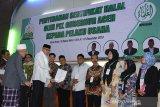 Plt Gubernur Aceh, Nova Iriansyah (kedua kiri) didampingi Wakil Ketua Majelis Permusyawaratan Ulama (MPU) Aceh, Tgk HM Daud Zamzami (kiri) menyerahkan sertifikat halal kepada sejumlah pelaku Usaha Kecil dan Menengah (UKM) di Kantor MPU Aceh, Aceh Besar, Aceh, Kamis (12/12/2019). Penyerahan sertifikat halal itu diberikan kepada sebanyak 28 pelaku UKM sebagai implementasi dari Qanun Aceh Nomor 8 tahun 2016 tentang Jaminan Produk Halal dan sekaligus upaya mewujudkan Aceh sebagai daerah wisata halal. Antara Aceh/Ampelsa.