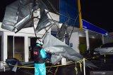 Petugas melihat reruntuhan bagian depan bangunan gedung Bank Mandiri yang rusak akibat angin kencang di Kota Madiun, Jawa Timur, Jumat (13/12/2019) malam. Bencana angin kencang mengakibatkan sejumlah pohon tumbang dan bangunan rusak. Antara Jatim/Siswowidodo/zk