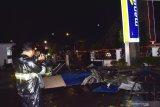 Wartawan mengambil gambar reruntuhan bagian depan bangunan gedung Bank Mandiri yang rusak akibat angin kencang di Kota Madiun, Jawa Timur, Jumat (13/12/2019) malam. Bencana angin kencang mengakibatkan sejumlah pohon tumbang dan bangunan rusak. Antara Jatim/Siswowidodo/zk